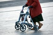 pic of rollator  - An elderly woman walking on the street with her walking frame - JPG
