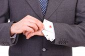 image of cheater  - Businessman with playing cards hidden under sleeve - JPG