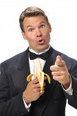 pic of emcee  - Humorous handsome Caucasian man in black tuxedo holds banana microphone and points finger at camera with white background - JPG