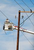 picture of lineman  - Power company lineman working on the instalation of power lines using a boom truck - JPG