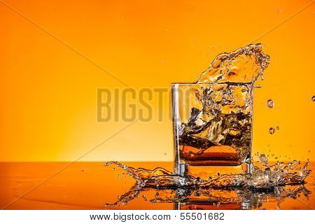 Glass of whiskey splashing out