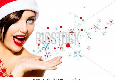 Christmas Woman. Beauty Model Girl in Santa Hat isolated on White Background. Funny Laughing Surprised Woman Blowing Snow Open Mouth. True Emotions. Red Lips. Beautiful Holiday Makeup.