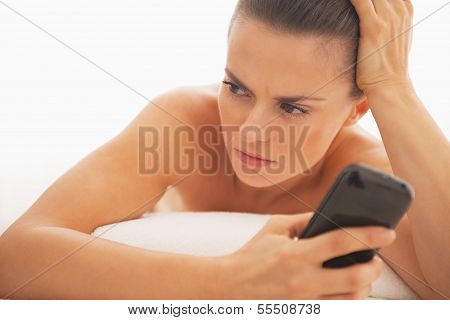 Frustrated Young Woman With Cell Phone Laying On Massage Table