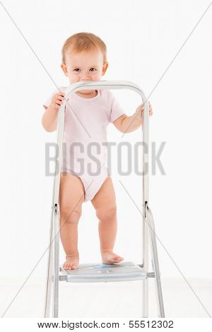 Impish little baby girl standing on top of ladder, smiling.