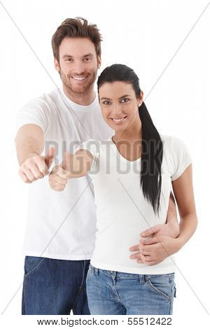 Happy young couple standing over white background, showing thumb up, smiling.