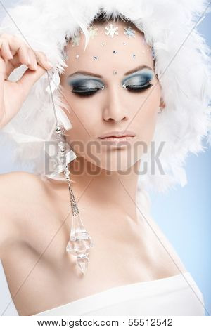 Luxurious winter beauty with crystal jewel and professional makeup with strasses.