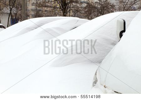 Snowy cars trapped in snowdrift, and blocked on parking