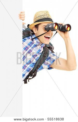Smiling male tourist loooking through binocular behind a blank panel isolated on white background