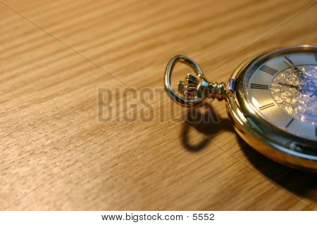 Golden Pocket Watch Against Wooden Plate.
