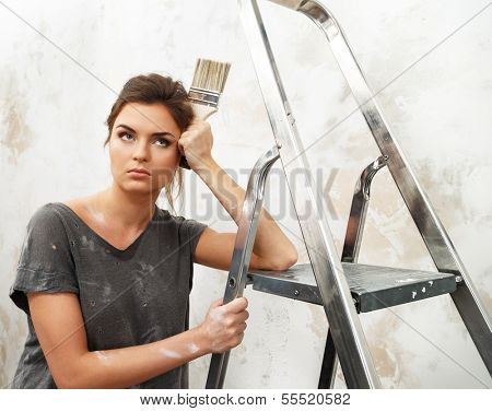 Disgruntled young brunette woman with ladder and painting brush