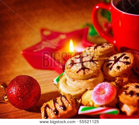 Closeup on tasty sweet homemade gingerbread with cup of tea, star shape candle, festive christmas decoration, traditional Christmastime dessert