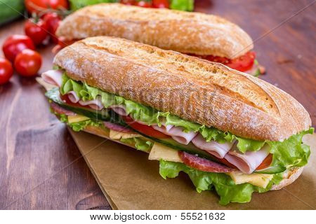 Long Baguette Sandwich with lettuce, slices of fresh tomatoes, cucumber, ham, salami and cheese