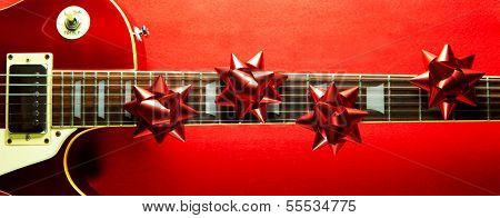 Red vintage solid body electric guitar with red ribbon bows on fretboard. A concept image for Christmas and holiday season music event.
