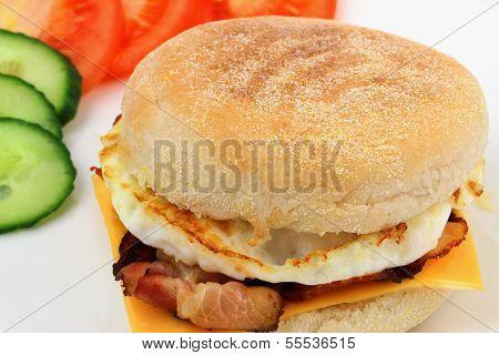 englische Muffins mit Spiegelei, Speck, Cheddar-Käse, Tomaten und Gurken