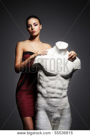 Young, rich and beautiful woman with the mannequin over the vintage background