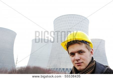 Engineer with protective helmet standing in front of nuclear power plant