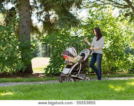 Full length of happy young woman with baby carriage using cell phone in park