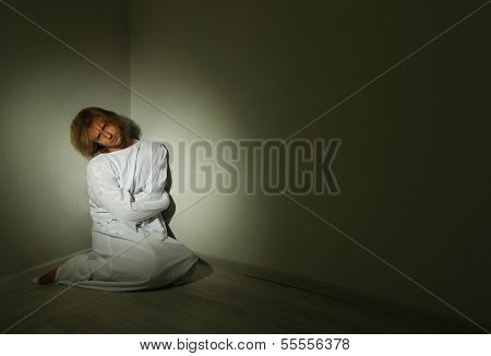 Mentally ill man in strait-jacket in room corner