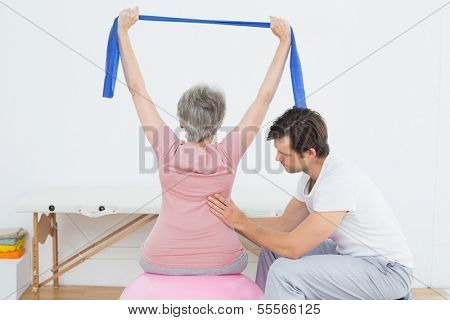 Senior woman sitting on yoga ball while working with a physical therapist
