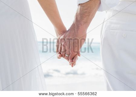 Bride and groom holding hands close up at the beach