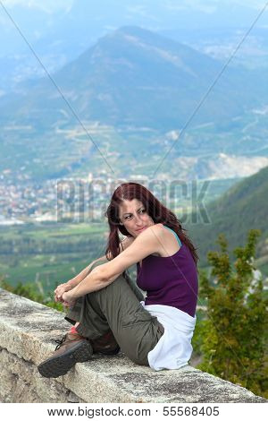 Woman Sitting On A Ledge.