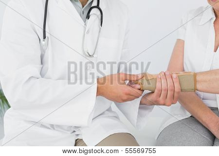 Close-up mid section of a male physiotherapist examining a woman's wrist in the medical office