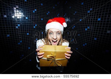 Portrait of glad businesswoman in Santa cap holding Chistmas gift