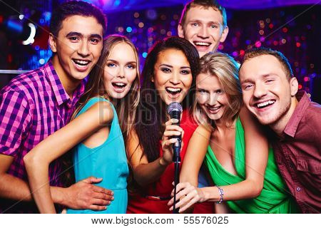 Portrait of happy girls and guys singing in microphone in the karaoke bar