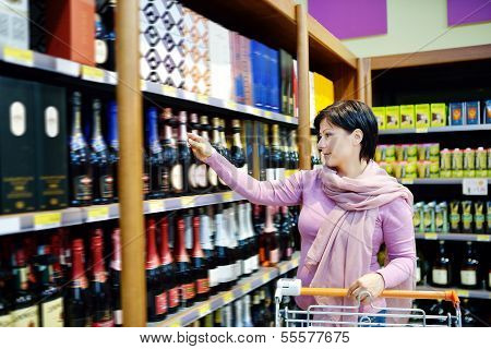 Woman Shopping And Choosing Liquor At Supermarket