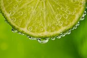 pic of macro  - Beautiful fresh slice of lime in the water with bubbles - JPG