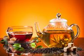 Teapot and cup with blooming tea on glass