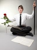 Young man with trumpet and red rose on gray background. Love and music. Valentine's day.