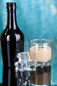 pic of bailey  - Baileys liqueur in bottle and glass on blue background - JPG