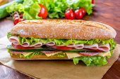 Long Baguette Sandwich with lettuce, slices of fresh tomatoes, ham, turkey breast and cheese