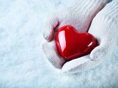 Female hands in white knitted mittens with a glossy red heart on a snow background.  Love and St. Va
