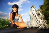 stock photo of inline skating  - Woman on rollerblades taking a rest on a sunny day - JPG