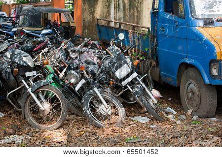 Old Broken Motorbikes And Car In Junkyard. India
