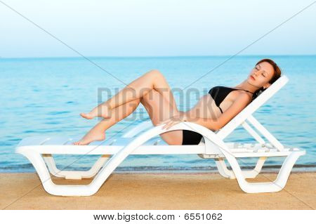 Lovely Girl laying near the sea