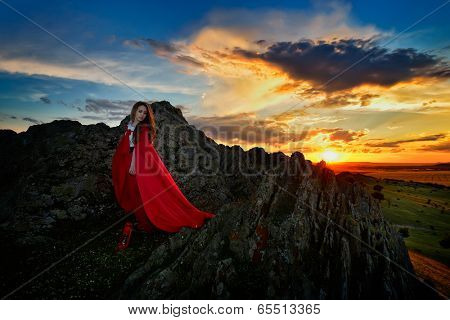 beautiful woman with red cloak in the sunset light in spring