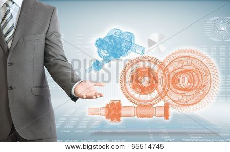 Businessman points hand on wire frame gears