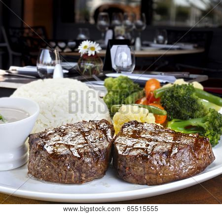 filet mignon with baked potato rice and vegetables