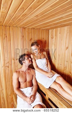Happy couple relaxing together in sauna of health resort spa