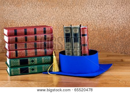 Graduation Mortarboard On Top Of Stack Of Books On Abstract Background Of Wall