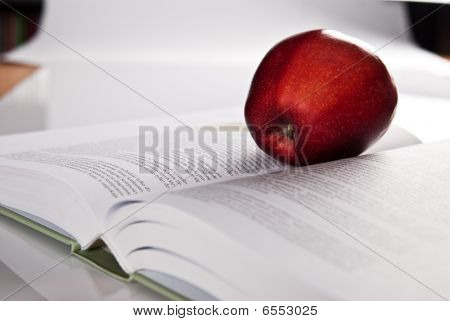 Open Hefty Book And Fresh Red Apple