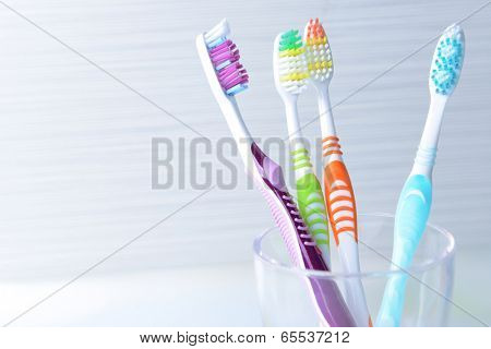 Toothbrushes in glass on table on light background