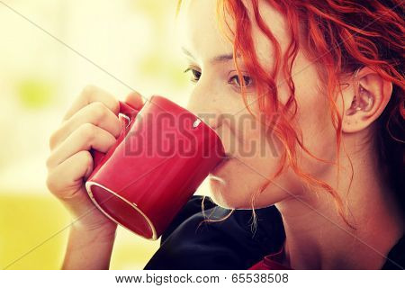 Beautiful deaf woman drinking coffee