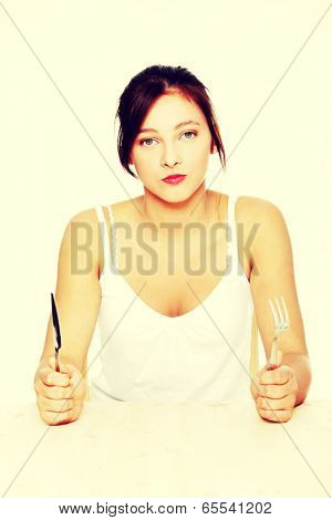 Hungry pretty caucasian teenage girl sitting behind the table with fork and knife.