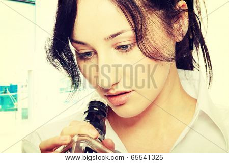 Alone young businesswoman in depression, drinking alcohol