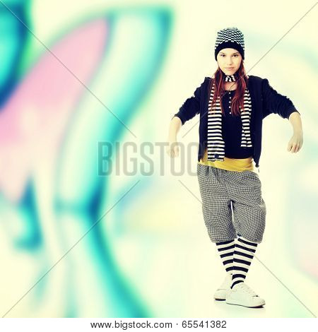 Young funky dancer against abstract grafitti background