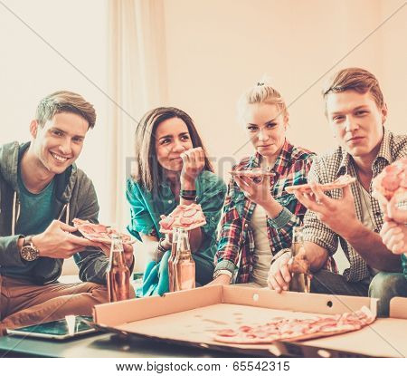 Group of young multi-ethnic friends with pizza and bottles of drink celebrating in home interior